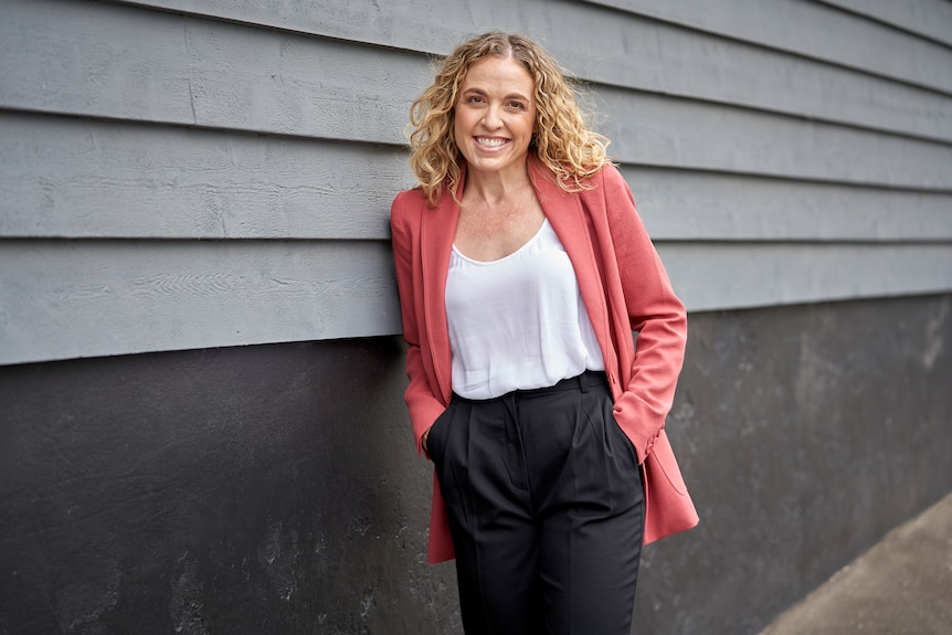 Woman in pink blazer and black pant smiling