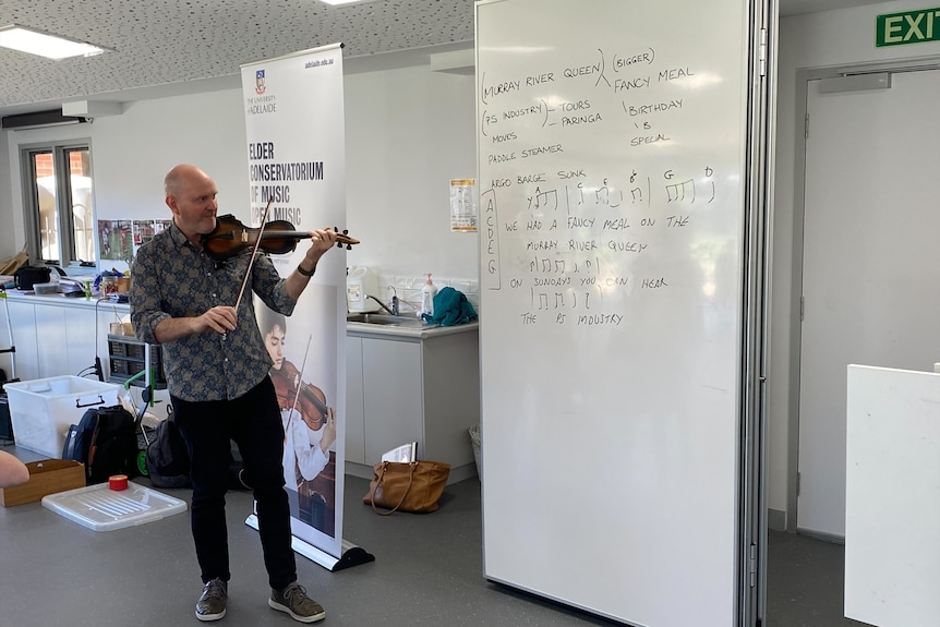 A man playing a violin in a classroom with a whiteboard with song lyrics.