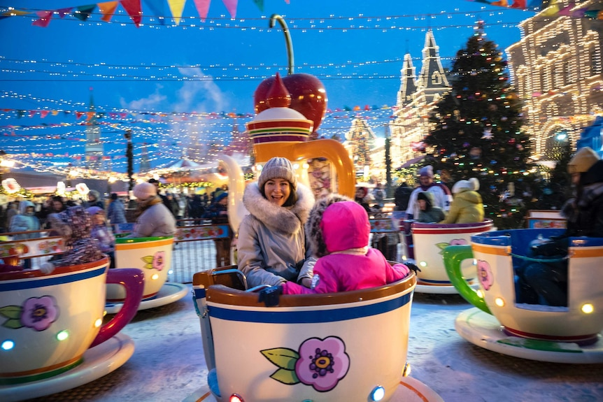 A woman and child spin on a tea cup ride in Red Square.