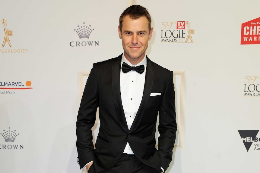 Roger Corser wears a black and white suit and tie on the logies red carpet.