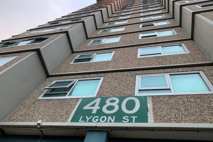 A ground view close to the public housing tower, looking up, with a '480 Lygon St' sign visible.