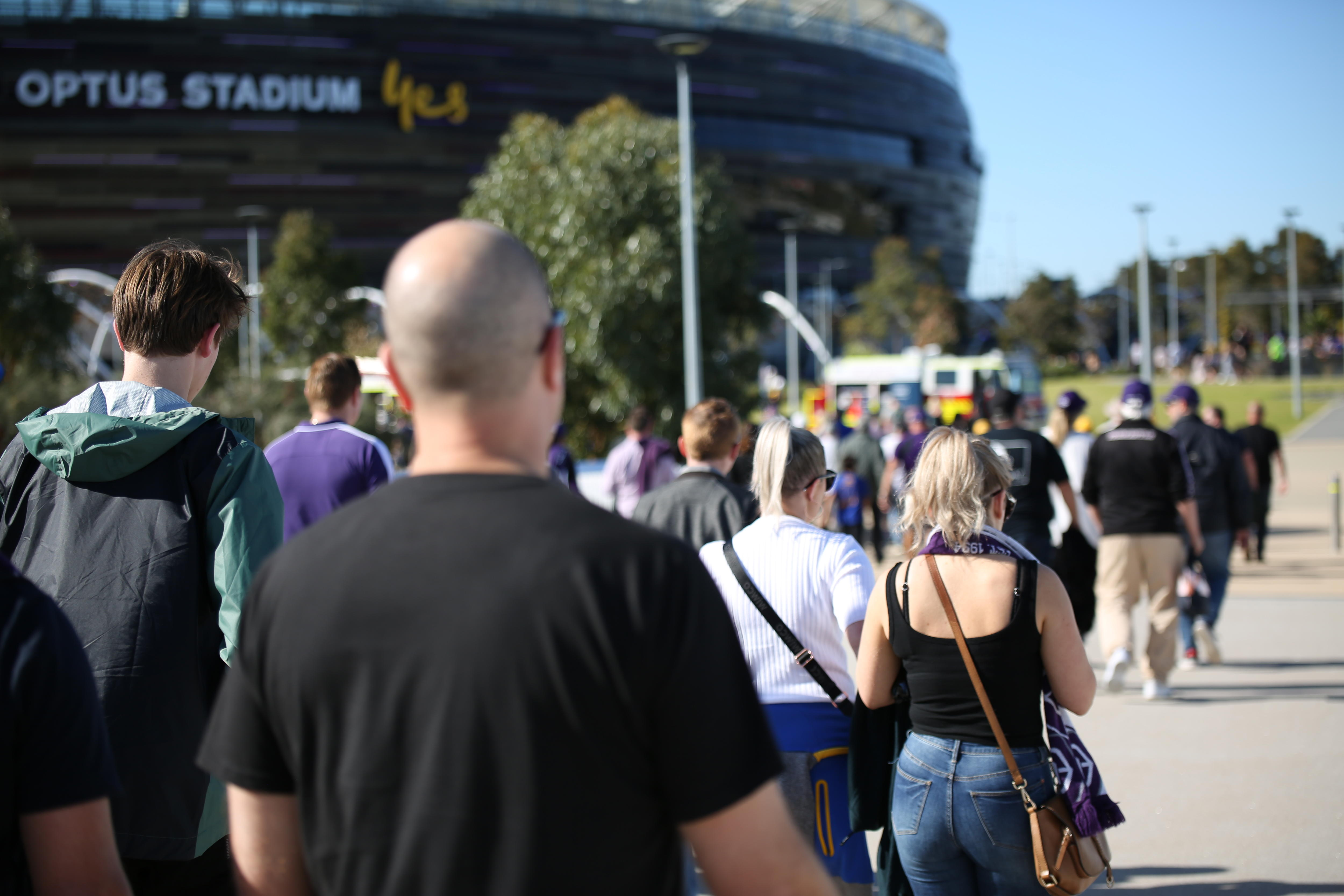 Crowds are walking along a footpath leading to Perth Stadium on a sunny day wearing Dockers scarves among other football merch