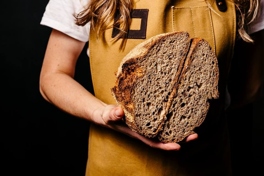 A woman holds a loaf of bread, she is wearing a mustard-coloured apron.