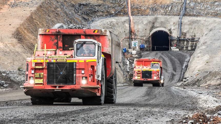Trucks emerge from the underground portal at the Nova nickel-copper mine.