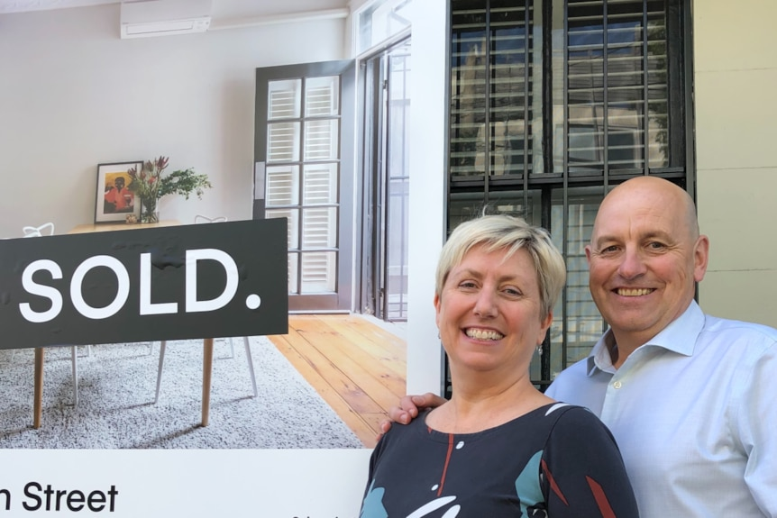 A middle aged couple stand in front of a sold sign