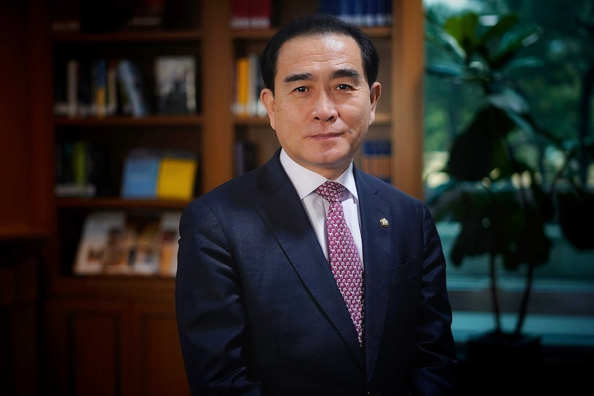 A Korean man in a suit standing in a nice office