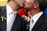 Two men in suits kiss.