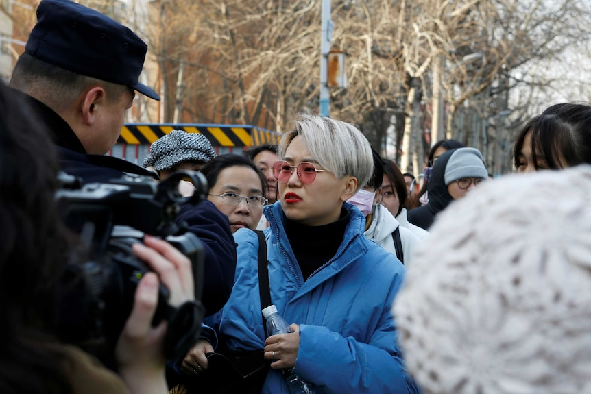 A young woman in a bright blue jacket holds a water bottle surrounded by a crowd as she talks to a police officer.