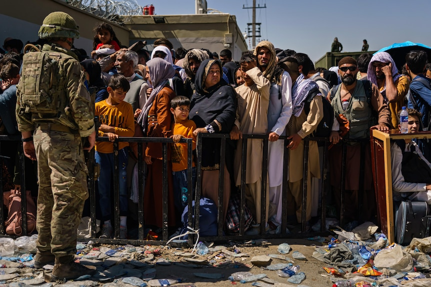 A soldier stands looking at dozens of men, women, and children standing behind a barrier. The people look concerned and tired.