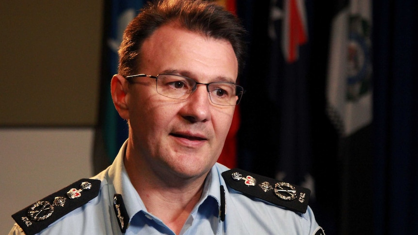 AFP Commissioner Reece Kershaw, in a uniform with flags hanging behind him in a room, speaks during an interview.
