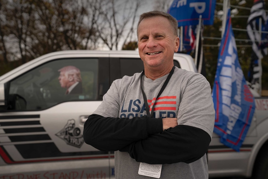 A man smiling with his arms folded across his chest in front of a car with Trump's photo in the window