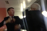 James Ashby and former One Nation senator Brian Burston scuffle in a grainy image.