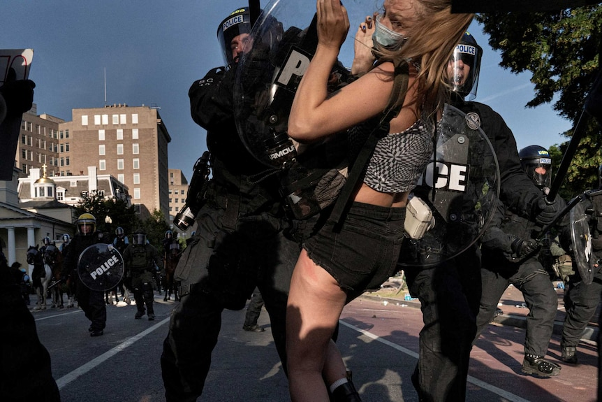 Riot police rush demonstrators as they clear Lafayette Park.
