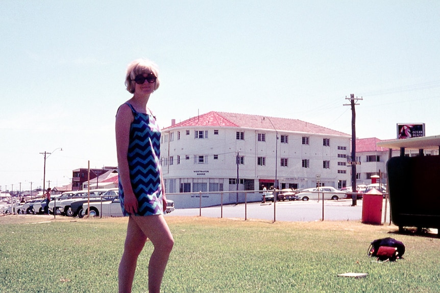 A woman in sunglasses and a dress with a white building in the background.