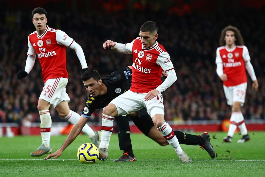 Two English Premier League players challenge for the ball during a match in London.