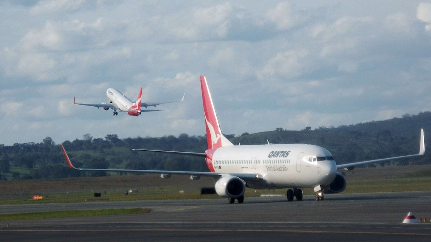A Qantas plan on a tarmac with another taking off in the distant background