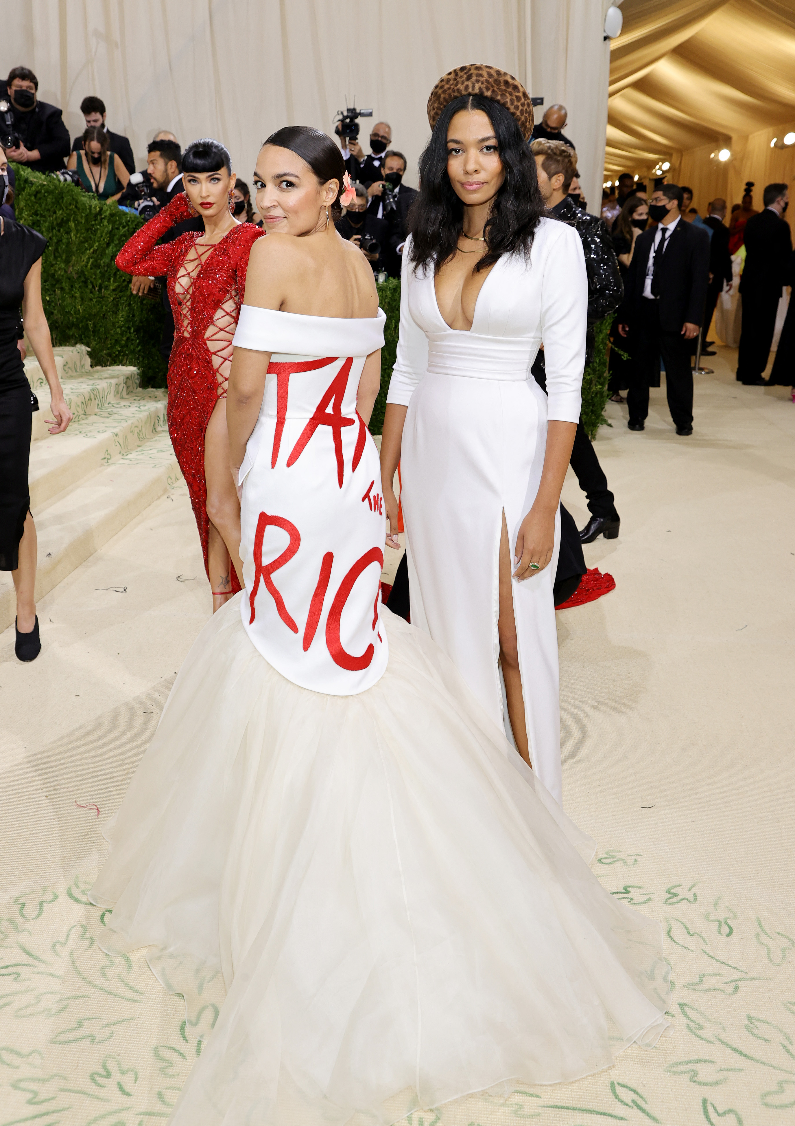 """Alexandria Ocasio-Cortez wears a white floor length dress with """"Tax the Rich"""" written in red letters."""