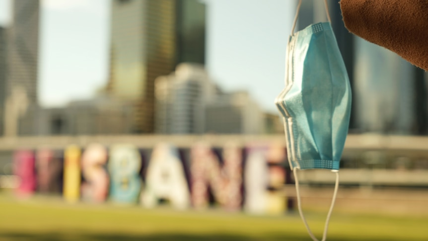 A person holds a mask in the air near Brisbane sign.