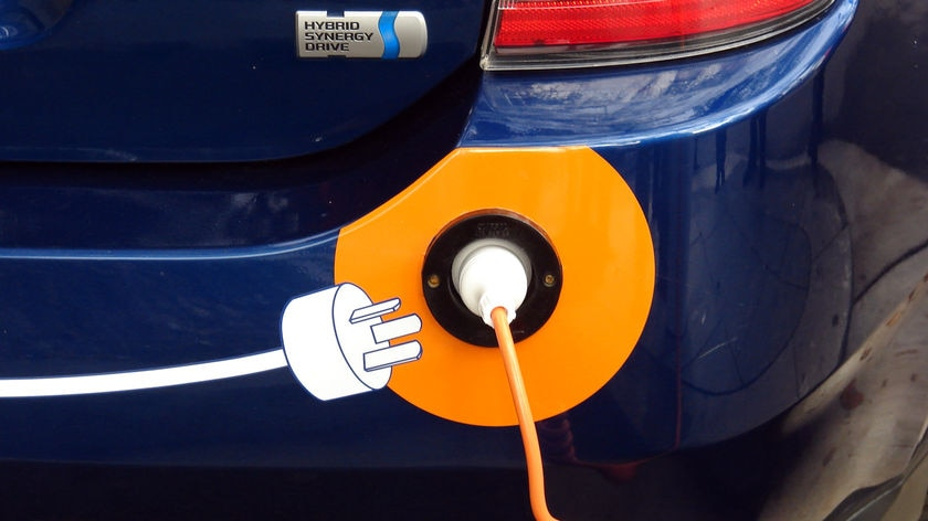 A hybrid car gets charged on the street