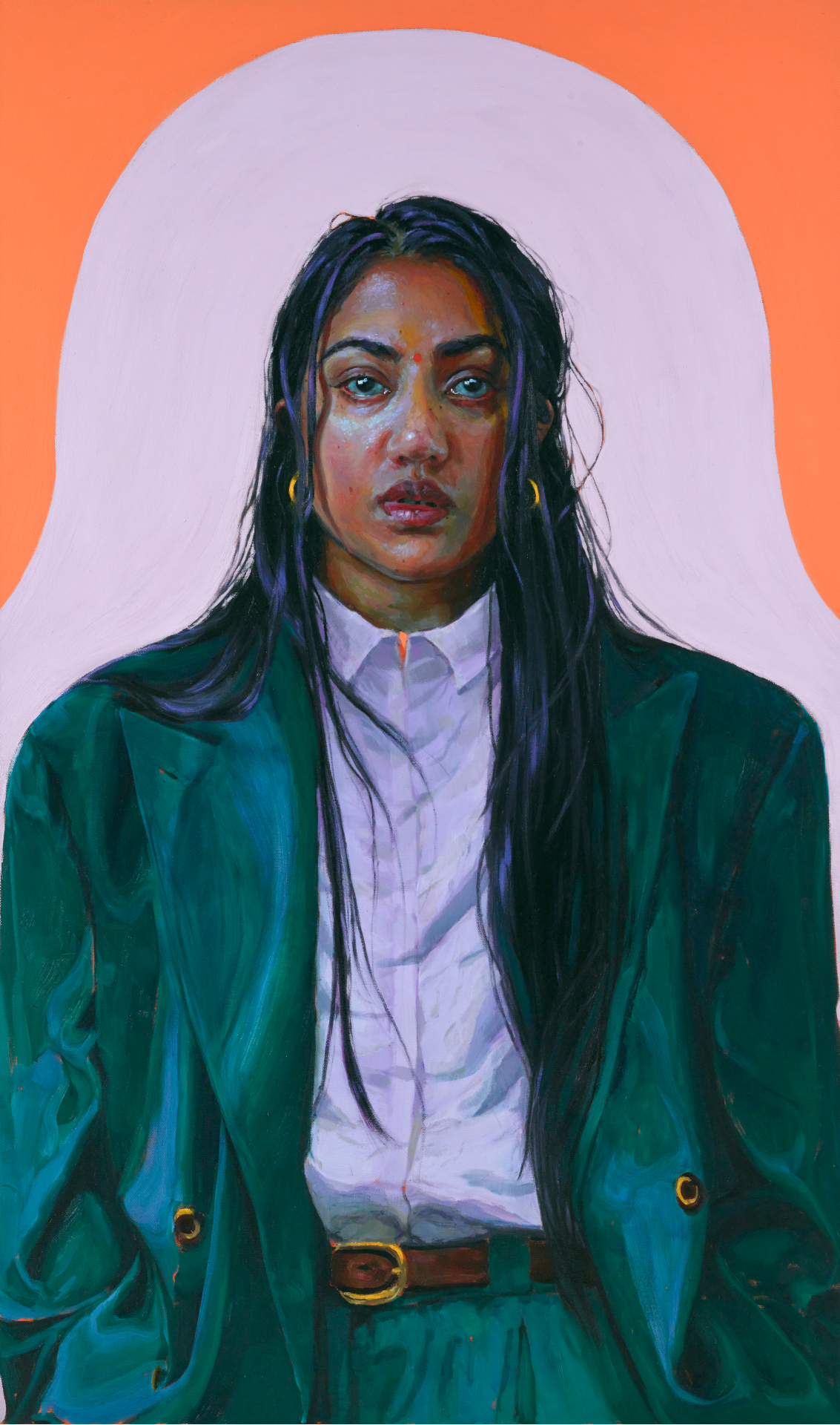 A self-portrait of Kirthna Selvaraj looking straight ahead and wearing an oversized green suit, with a white button-down