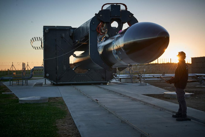 A man stands in front of a rocket getting ready for luanch