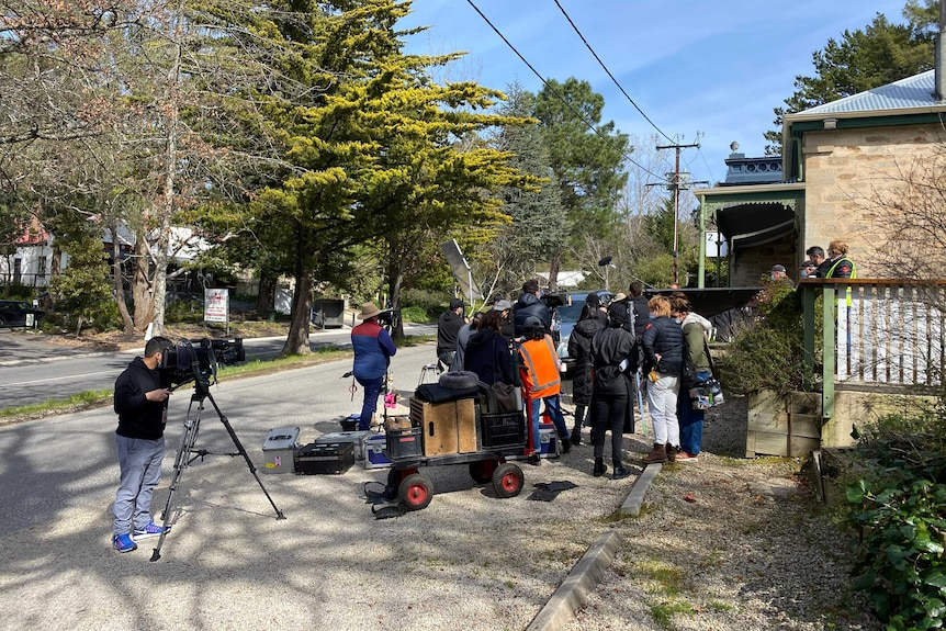 A film crew with cameras shooting near buildings.