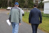 The back view of two men walking towards a car on a rural property