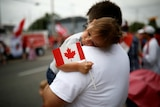 A child waves a Canadian flag while lying on a man's shoulder.
