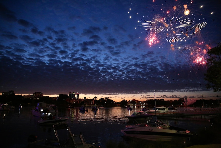 A late sunset photo of fire works exploding in a cloudy sky over the Swan River above several boats before the Perth CBD skyline