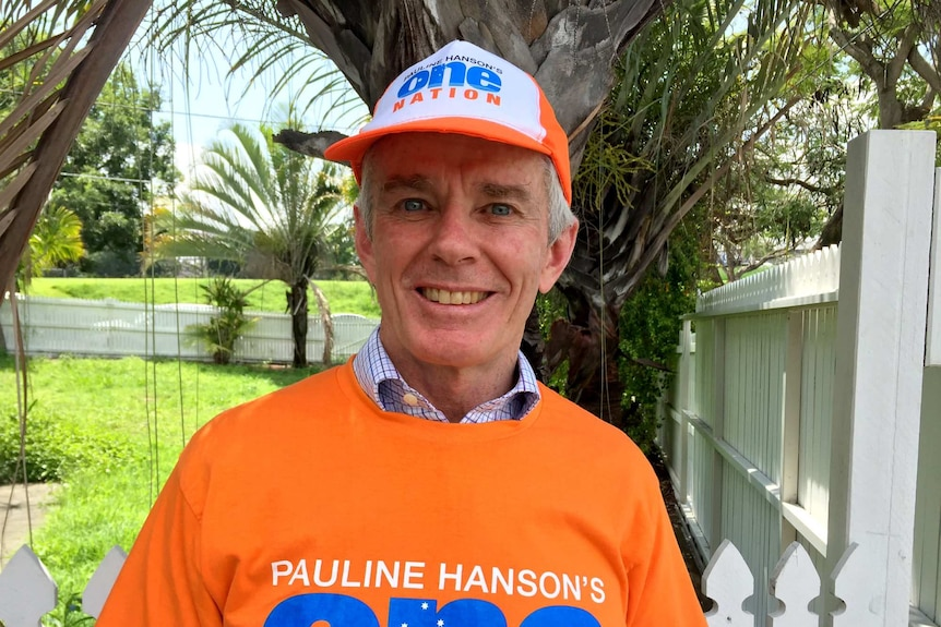 Malcolm Roberts smiles while wearing a One Nation t-shirt and cap