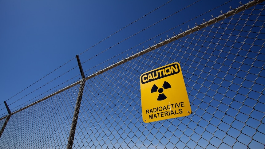 A sign on a fence saying caution radioactive materials