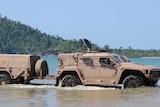 An Australian Army Hawkei drives through the shallows at a beach.