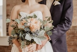 Bride holding flowers, and groom, faces obscured.