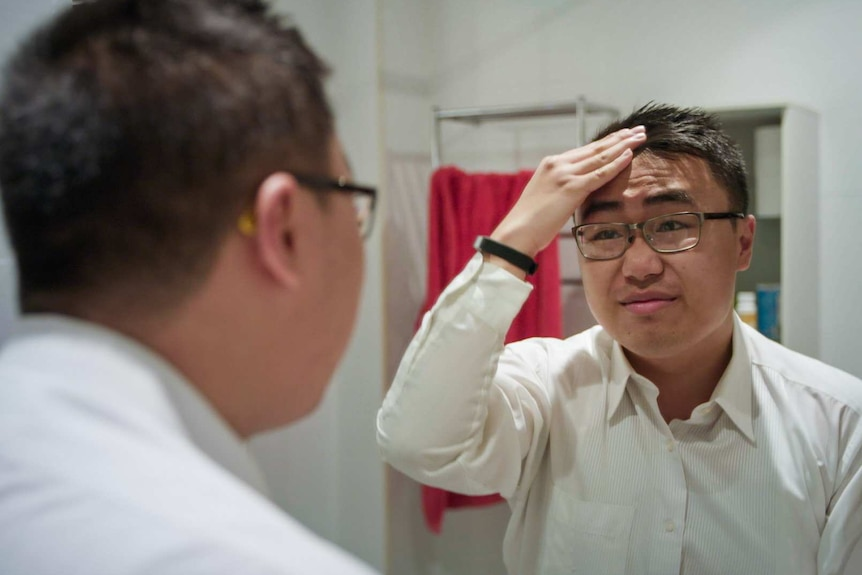 A young man is fixing his hair in the mirror as he gets ready to go out