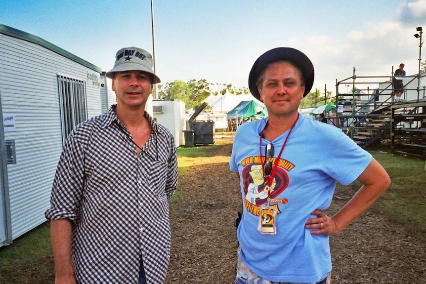 Two men stand between portable buildings at a musical festival.