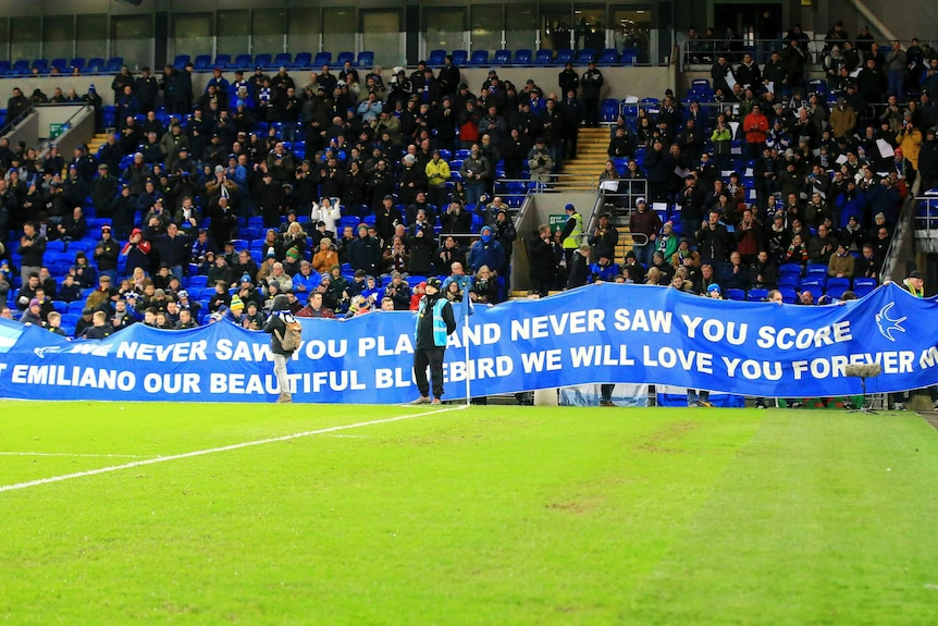 Fans hold a banner in tribute to Italian footballer Emiliano Sala at a Premier League game.