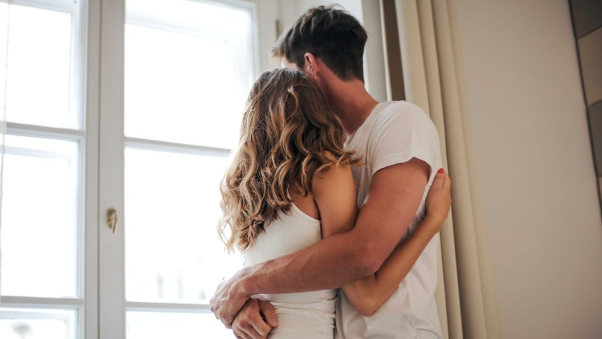 Man and woman embrace standing up in a story about how to support your partner if they experience pain during sex.