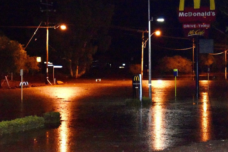 Street lights illuminate a flooded road in front of a fast food drive through.
