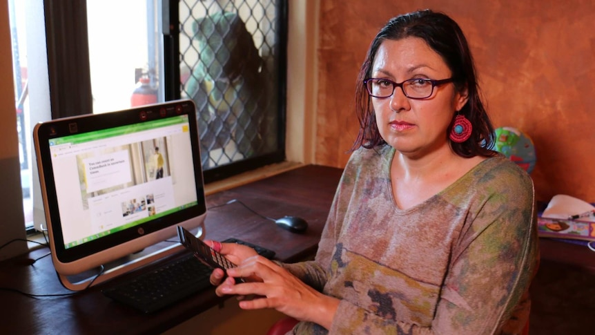Woman sitting in front of computer and holding phone, looking worried
