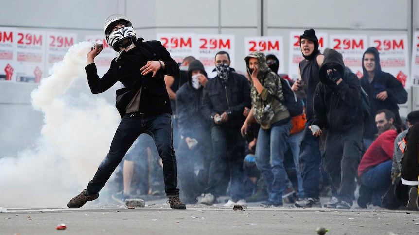 A demonstrator throws back a teargas canister during heavy clashes with riot police in Barcelona