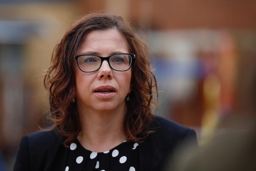 A woman with brown curly hair and glasses mid-sentence with everything else around her blurred out