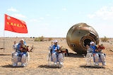 Three astronauts sit in reclining chairs in the desert after landing from a mission.