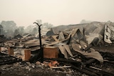 The ruins of a home destroyed by fire lies smouldering in Wingello.