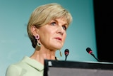 Julie Bishop speaks into two microphones at a lectern. She is wearing a beige coloured suit and jewelled earrings.