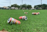 Image of multiple empty cans of beer that have been discarded on a sporting oval in Broome.