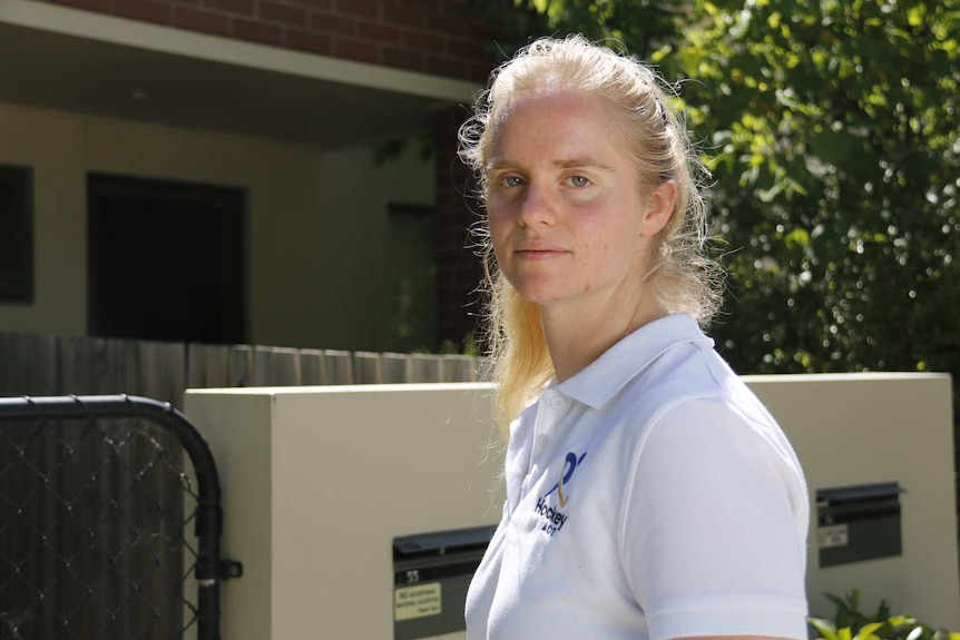 A woman stands outside a unit in Canberra.