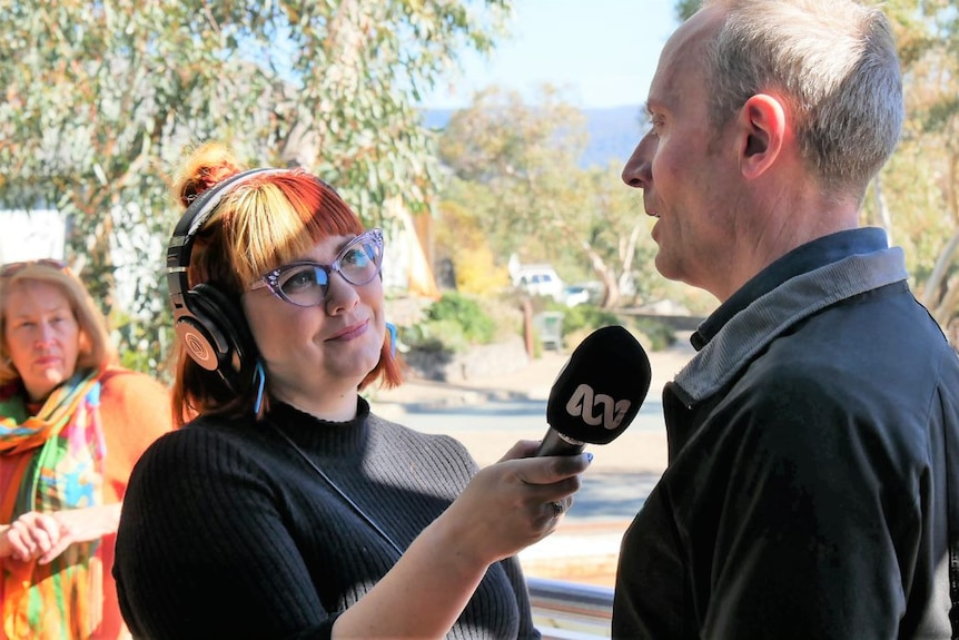 Kia Handley wearing headphones and holding mic while interviewing a man on a street for the ABC.