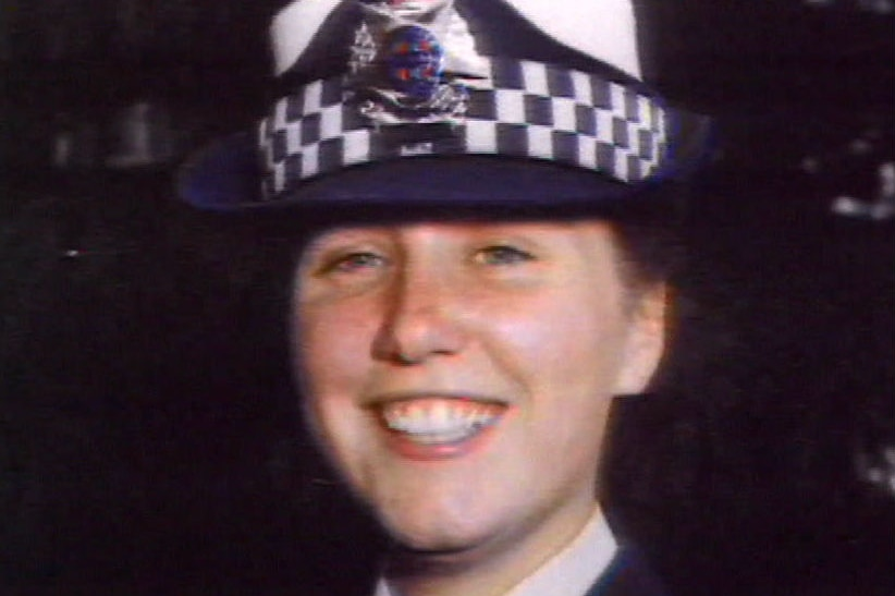Angela Taylor wears a police uniform and hat.