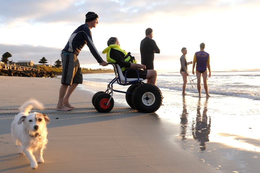 Man in wheel chair being pushed into ocean
