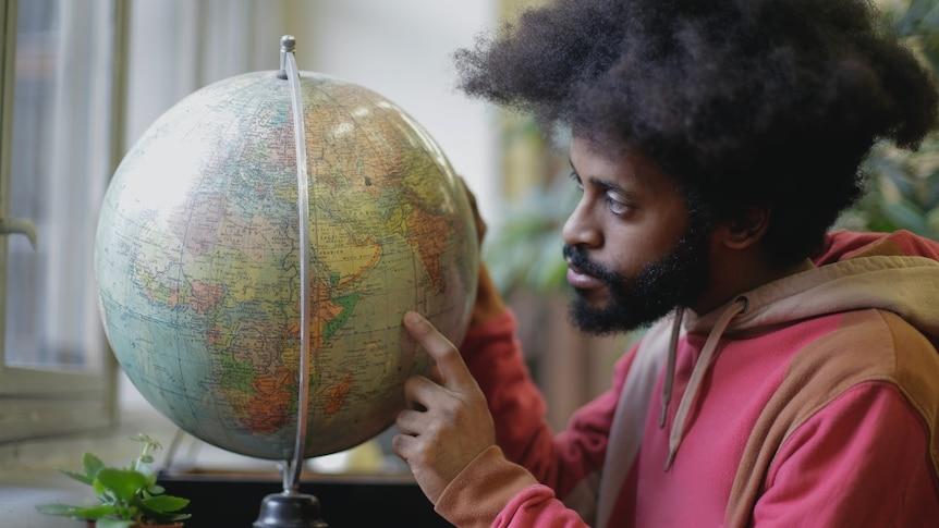A man points at a world globe